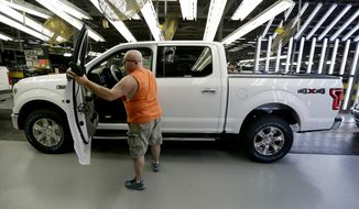 FILE- In this March 13, 2015, file photo, a worker inspects a new 2015 aluminum-alloy body Ford F-150 truck at the company's Kansas City Assembly Plant in Claycomo, Mo. Under pressure from U.S. safety regulators, Ford is recalling about 2 million F-150 pickups in North America because the seat belts can cause fires. The recall covers certain trucks from the 2015 through 2018 model years. (AP Photo/Charlie Riedel, File)