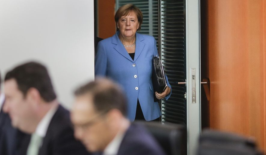 German Chancellor Angela Merkel arrives for the weekly cabinet meeting of the German government at the chancellery in Berlin, Wednesday, Sept. 5, 2018. In the fore ground left Labor Minister Hubertus Heil and right Foreign Minister Heiko Maas. (AP Photo/Markus Schreiber)