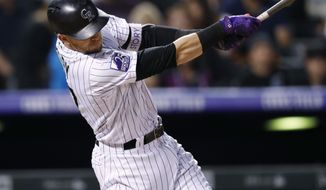 Colorado Rockies' Trevor Story follows through on a solo home run off San Francisco Giants starting pitcher Andrew Suarez during the sixth inning of a baseball game Wednesday, Sept. 5, 2018, in Denver. (AP Photo/David Zalubowski)