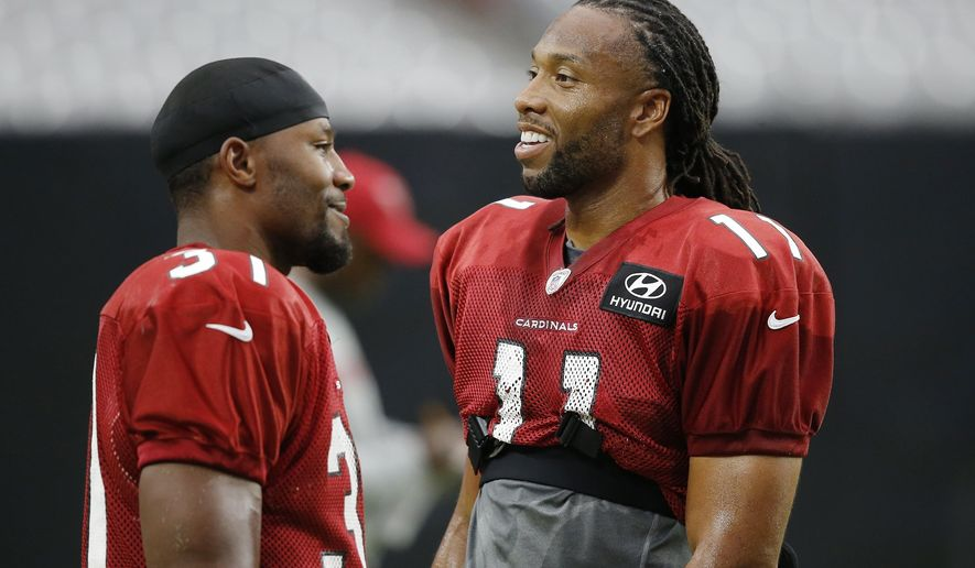 FILE - In this Aug. 2, 2018, file photo, Arizona Cardinals wide receiver Larry Fitzgerald (11) talks with running back David Johnson (31) during an NFL football practice, in Glendale, Ariz. The Washington Redskins will be trying to give coach Jay Gruden his first victory in a season opener in five tries when they face the Cardinals in Arizona on Sunday. Sept. 9, 2018. The team Gruden will face is something of a mystery, with a rebuilt offense and redesigned defense under new coach Steve Wilks.(AP Photo/Ross D. Franklin, File)