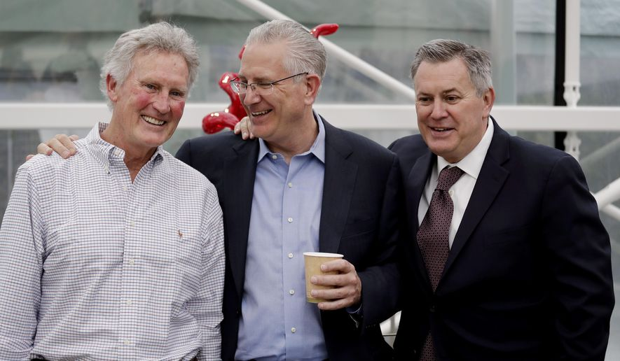 FILE - In this April 11, 2018, file photo, Tod Leiweke, center, chats with his brothers Tracey Leiweke, left, and Tim Leiweke as they pose for a photo following a news conference naming Tod Leiweke as the president and CEO for a prospective NHL expansion hockey team, in Seattle. NHL deputy commissioner Bill Daly says December is the earliest the Board of Governors will vote on potential expansion to Seattle. (AP Photo/Elaine Thompson, File)