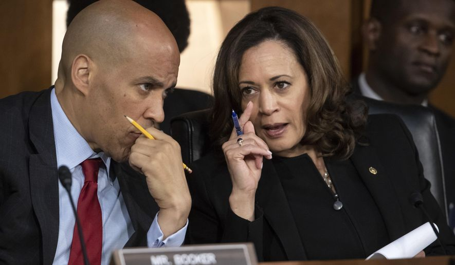 Sen. Cory Booker, D-N.J., left, and Sen. Kamala Harris, D-Calif., confer as Supreme Court nominee Brett Kavanaugh testifies before the Senate Judiciary Committee on the third day of his confirmation hearing, on Capitol Hill in Washington, Thursday, Sept. 6, 2018. (AP Photo/J. Scott Applewhite)