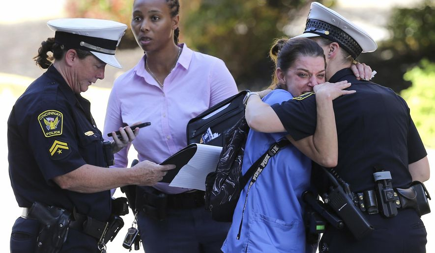 A woman is comforted by authorities stationed outside the University of Cincinnati Medical Center's Emergency room following a shooting in downtown Cincinnati that left at least four dead, including the gunman, and several injured, Thursday, Sept. 6, 2018, in Cincinnati. (Kareem Elgazzar/The Cincinnati Enquirer via AP)
