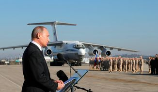 FILE - In this Dec. 12, 2017, file photo, Russian President Vladimir Putin addresses the troops at the Hemeimeem air base in Syria. When the presidents of Russia, Turkey and Iran meet in Tehran Friday, Sept. 7, all eyes will be on their diplomacy averting a bloodbath in Idlib, Syria's crowded northwestern province and last opposition stronghold. The three leaders whose nations are all under U.S. sanctions have an interest in working together, but Idlib is complicated and they have little common ground. (Mikhail Klimentyev/Pool Photo via AP, File)