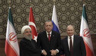 FILE- In this April 4, 2018, file photo, Iran's President Hassan Rouhani, left, Russia's President Vladimir Putin, right, and Turkey's President Recep Tayyip Erdogan join hands after a joint press conference in Ankara, Turkey. When the presidents of Russia, Turkey and Iran meet in Tehran on Friday, Sept. 7, all eyes will be on their diplomacy averting a bloodbath in Idlib, Syria's crowded northwestern province and last opposition stronghold. The three leaders whose nations are all under U.S. sanctions have an interest in working together, but Idlib is complicated and they have little common ground. (AP Photo/Burhan Ozbilici, File)