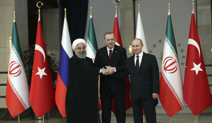 In this April 4, 2018, file photo, Iran's President Hassan Rouhani, left, Russia's President Vladimir Putin, right, and Turkey's President Recep Tayyip Erdogan lock hands during a group photo in Ankara, Turkey. When the presidents of Russia, Turkey and Iran meet in Tehran Friday, Sept. 7, all eyes will be on their diplomacy averting a bloodbath in Idlib, Syria's crowded northwestern province and last opposition stronghold. The three leaders whose nations are all under U.S. sanctions have an interest in working together, but Idlib is complicated and they have little common ground. (Tolga Bozoglu/Pool Photo via AP, File)