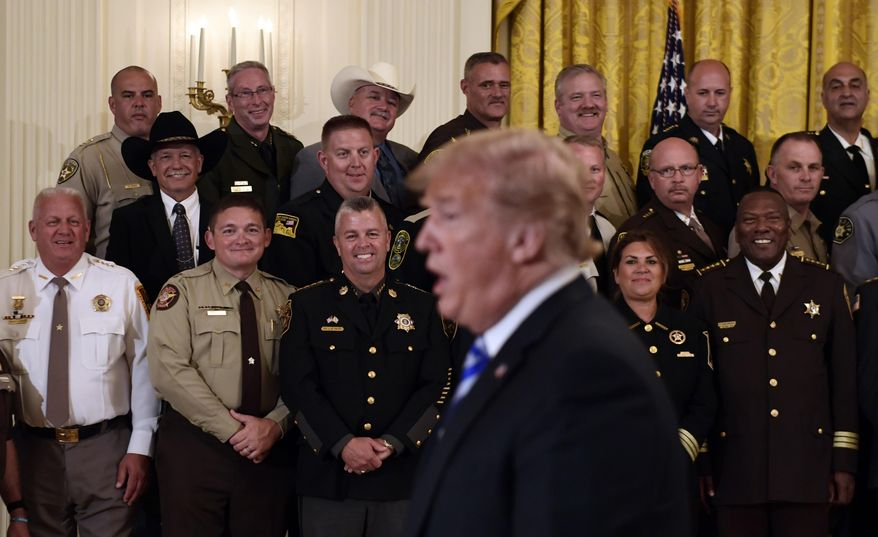 Sheriffs listens as President Donald Trump responds to a reporters question during an event in the East Room of the White House in Washington, Wednesday, Sept. 5, 2018. (AP Photo/Susan Walsh)