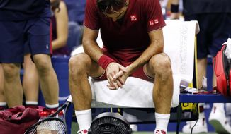 FILE - In this early Tuesday, Sept. 4, 2018, file photo, Roger Federer, of Switzerland, sits in front of a fan during a changeover in his match against John Millman, of Australia, during the fourth round of the U.S. Open tennis tournament, in New York. It's not just the heat, it's the humidity at this most uncomfortable of U.S. Opens. Don't sweat the small stuff? Try telling that to Roger Federer, Rafael Nadal, Novak Djokovic and other players who've been dripping and drenched at the year's last Grand Slam tournament. (AP Photo/Jason DeCrow, File)
