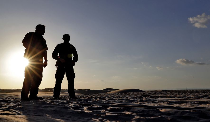A pair of U.S. Customs and Border Patrol agents look at tracks in the sand along the floating fence that makes up the international border with Mexico, Wednesday, July 18, 2018 in Imperial County, Calif. 126-miles of border cuts through the Yuma Sector where thousands of families and unaccompanied children are continuing to cross into Arizona and California even after learning of the government's family separation policy upon apprehension. (AP Photo/Matt York)
