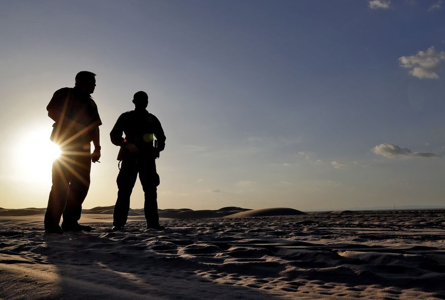 A pair of U.S. Customs and Border Patrol agents look at tracks in the sand along the floating fence that makes up the international border with Mexico, Wednesday, July 18, 2018, in Imperial County, Calif. About 126-miles of border cuts through the Yuma Sector where thousands of families and unaccompanied children are continuing to cross into Arizona and California even after learning of the government's family separation policy upon apprehension. (AP Photo/Matt York) ** FILE **