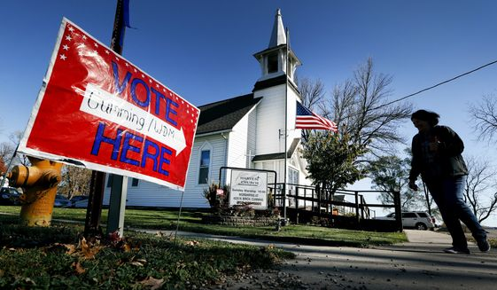 In this Tuesday, Nov. 8, 2016 file photo, a local resident leaves a church after voting in the general election in Cumming, Iowa. Religion's role in politics and social policies is in the spotlight heading toward the midterm elections, yet relatively few Americans consider it crucial that a candidate be devoutly religious or share their religious beliefs, according to an AP-NORC national poll conducted Aug. 16-20, 2018. (AP Photo/Charlie Neibergall) **FILE**