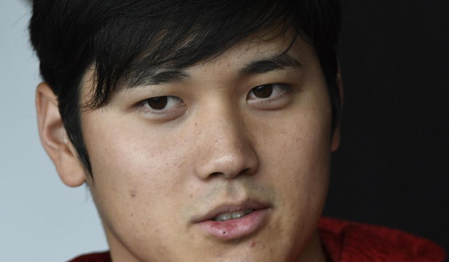 Los Angeles Angels' Shohei Ohtani talks to the media before a baseball game against the Chicago White Sox, Friday, Sept. 7, 2018, in Chicago. (AP Photo/David Banks)