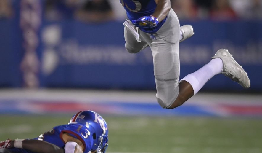 Kansas Jayhawks wide receiver Kwamie Lassiter II (83) goes high to avoid other players during a punt return against Nicholls State during the second half of an NCAA college football game in Lawrence, Kan., Saturday, Sept. 1, 2018. (AP Photo/Reed Hoffmann)
