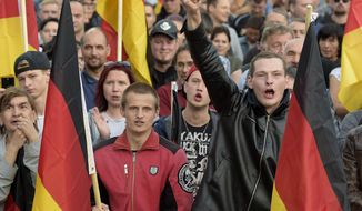 People attend a demonstration in Chemnitz, eastern Germany, Friday, Sept.7, 2018, after several nationalist groups called for marches protesting the killing of a German man two weeks ago, allegedly by migrants from Syria and Iraq. (AP Photo/Jens Meyer)