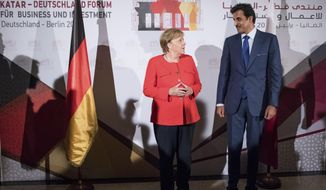 German Chancellor Angela Merkel, left, and the Emir of Qatar Tamim bin Hamad Al Thani, right, pose for a photo prior to the 'Qatar - Germany Forum For Business And Investment' in Berlin, Germany, Friday, Sept. 7, 2018. (Bernd von Jutrczenka/pool photo via AP)