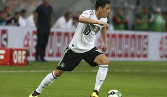 FILE - In this June 2, 2018 file photo Germany's Mesut Ozil runs with the ball during a friendly soccer match between Austria and Germany in Klagenfurt, Austria. (AP Photo/Ronald Zak, file)