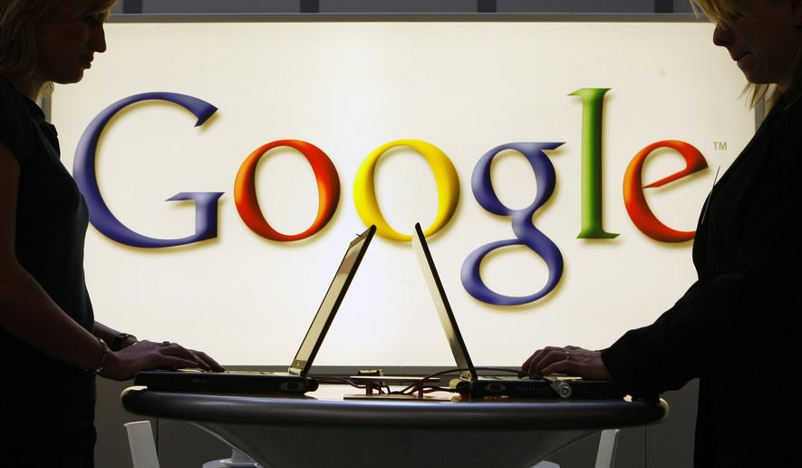 In this April 17, 2007, file photo exhibitors of the Google company work in front of a illuminated sign at the industrial fair Hannover Messe in Hanover, Germany. (AP Photo/Jens Meyer, File)