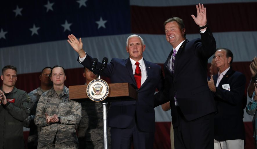 Vice President Mike Pence joins Sen. Dean Heller, R-Nev, on stage in a hanger at Nellis Air Force Base in Las Vegas, Friday, Sept. 7, 2018. (Steve Marcus/Las Vegas Sun via AP)