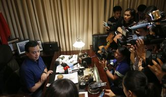 Philippine opposition Senator Antonio Trillanes IV, left, is interviewed by the media inside his office where he remains holed up Friday, Sept. 7, 2018 in the Philippine Senate in suburban Pasay city, south of Manila, Philippines. Trillanes took refuge in the legislature to avoid an arrest order by President Rodrigo Duterte four days ago and has asked the Supreme Court to declare the move illegal. (AP Photo/Bullit Marquez)