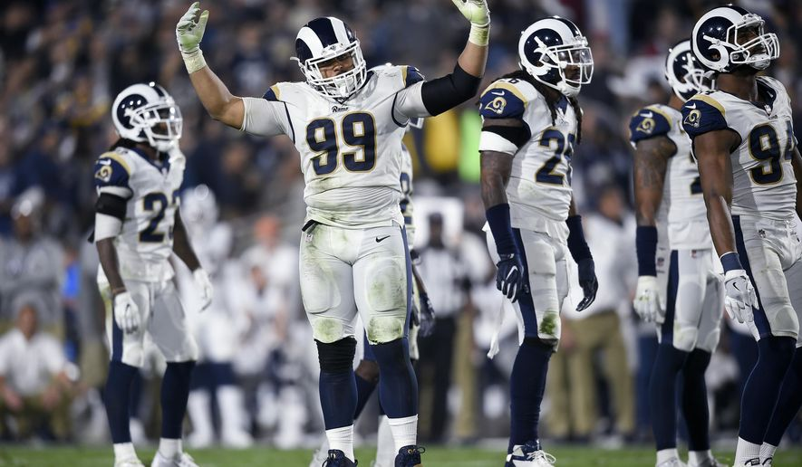 FILE - In this Jan. 6, 2018, file photo, Los Angeles Rams defensive tackle Aaron Donald (99) cheers on the crowd during the first half of the team'sNFL football wild-card playoff game against the Atlanta Falcons in Los Angeles. Donald, Ndamukong Suh and fellow starting defensive lineman Michael Brockers are together in practice for the first time this week while the Rams prepare for their season-opening trip to Oakland on Monday night. New Rams cornerbacks Marcus Peters and Aqib Talib also are eager to get on the field after barely playing in the preseason to see if this defense can live up to its enormous potential. (AP Photo/Kelvin Kuo, File)