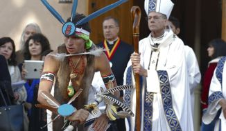 Dezmund Marcus of Ohkay Owingeh, N.M., performs the butterfly dance at the outset of an annual autumn festival in front of a crowd, including Roman Catholic Archbishop John Wester, right, on Friday, Sept. 7, 2018, in Santa Fe, N.M. Civic and Native American leaders this year agreed to cancel the traditional re-enactment of a 17th century conquistador reclaiming Santa Fe after a Native American revolt. Public statues and tributes to early Spanish conquerors have encountered mounting criticism tied to the brutal treatment of American Indians centuries ago by Spanish soldiers and missionaries. (AP Photo/Morgan Lee)