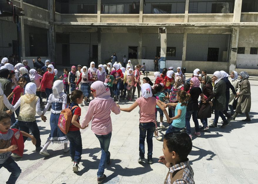 In this Wednesday, Sept 5, 2018 photo, Syrian students play in the courtyard of a school in the town of Douma, in the eastern Ghouta region, near the Syrian capital Damascus, Syria. Millions of Syrian children return to school as the country's conflict simmers down. The Syrian government is keen to project a sense of normalcy, opening hundreds of newly renovated schools and calling on students to wear uniforms, which were shed in years of chaos. But humanitarians say the war is far from over, particularly its scars on children. (AP Photo)