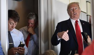 White House Deputy Press Secretary Hogan Gidley, left, and White House Deputy Chief of Staff for Communications, Bill Shine, center, listen as President Donald Trump talks to reporters while in flight from Billings, Mont., to Fargo, N.D., Friday, Sept. 7, 2018. (AP Photo/Susan Walsh)