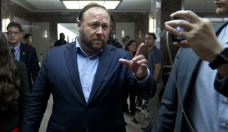 In this Wednesday, Sept. 5, 2018, file photo, Alex Jones, the right-wing conspiracy theorist, walks the corridors of Capitol Hill after listening to Facebook COO Sheryl Sandberg and Twitter CEO Jack Dorsey testify before the Senate Intelligence Committee on 'Foreign Influence Operations and Their Use of Social Media Platforms' on Capitol Hill, in Washington. Twitter's permanent ban of conspiracy-monger Alex Jones on Thursday again underscored the difficulty many social-media services face in trying to consistently apply their rules against harassment and other bad behavior. (AP Photo/Jose Luis Magana, File)