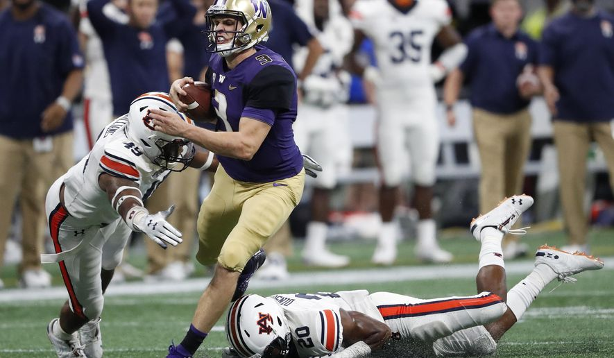 Washington quarterback Jake Browning (3) is stopped by Auburn's Darrell Williams (49) and Jeremiah Dinson (20) after running for a first down during the second half of an NCAA college football game Saturday, Sept. 1, 2018, in Atlanta. Auburn won 21-16. (AP Photo/John Bazemore)