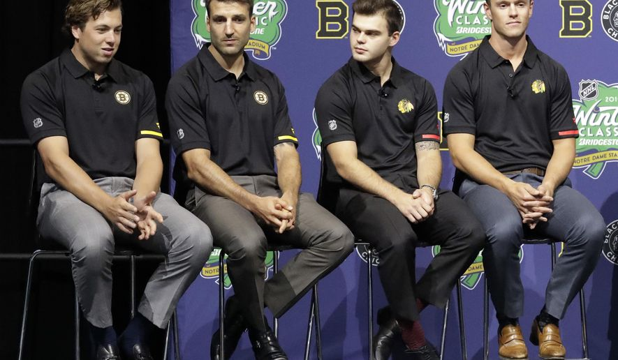Boston Bruins' Charlie McAvoy, left, speaks as teammate Patrice Bergeron, second from left, and Chicago Blackhawks' Alex DeBrincat and Jonathan Toews, right, listen during a news conference Thursday, Sept. 6, 2018, in Chicago about the NHL Winter Classic hockey game. The Bruins will play the Blackhawks at Notre Dame Stadium on New Year's Day in South Bend, Ind. (AP Photo/Nam Y. Huh)