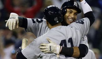 Detroit Tigers' Victor Reyes celebrates with teammate Victor Martinez after scoring on a wild pitch during the ninth inning to defeat the St. Louis Cardinals 4-3 in a baseball game, Saturday, Sept. 8, 2018, in Detroit. The Tigers and Cardinals are wearing uniforms from 1968. (AP Photo/Duane Burleson)