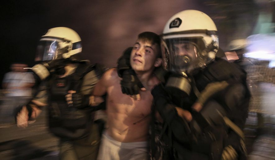 A protester is detained by riot policemen during clashes at the northern Greek city of Thessaloniki, Saturday, Sept. 8, 2018. Police in northern Greece have clashed with protesters outside an international trade fair where prime minister Tsipras made a keynote speech. (AP Photo/Dimitris Tosidis)