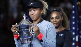 Naomi Osaka, of Japan, holds the trophy after defeating Serena Williams in the women's final of the U.S. Open tennis tournament, Saturday, Sept. 8, 2018, in New York. (AP Photo/Adam Hunger)