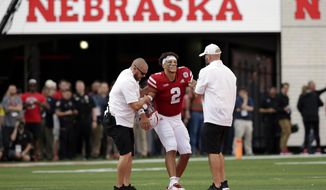 Nebraska trainers help injured quarterback Adrian Martinez (2) off the field during the second half of an NCAA college football game against Colorado in Lincoln, Neb., Saturday, Sept. 8, 2018. Colorado won 33-28. (AP Photo/Nati Harnik)