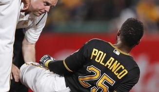 Pittsburgh Pirates trainer Bryan Housand, left, looks over Gregory Polanco's injured leg in the sixth inning of a baseball game against the Miami Marlins, Friday, Sept. 7, 2018, in Pittsburgh. (AP Photo/Keith Srakocic)
