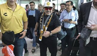 In this handout photo provided by Prensa Club Dorados de Sinaloa, Argentine soccer legend Diego Maradona walks through the airport in Culiacan, Mexico, Saturday, Sept. 8, 2018. Maradona arrived in northern Mexico Saturday afternoon, to begin his new job as head coach of the second-tier Mexican soccer club Dorados of Sinaloa. Pictured left is club president, Jose Antonio Nunez. (Prensa Club Dorados de Sinaloa via AP)