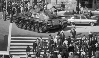 FILE - In this Oct. 27, 1979, file photo, people walk beside a South Korean army tank after martial law was declared following the death of South Korean President Park Chung-hee in Seoul, South Korea. Former Associated Press photojournalist Kim Chonkil, whose images captured South Korea's turbulent transition from dictatorship to democracy, has died. He was 89. Kim's son, Kim Kuchul, confirmed he died in New York on Thursday, Sept. 6, 2018. (AP Photo/Kim Chonkil, File)