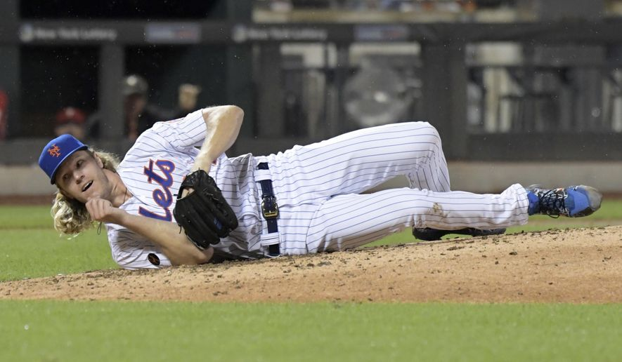 New York Mets pitcher Noah Syndergaard hits the dirt after being hit on the ribs by a ball hit by Philadelphia Phillies' Cesar Hernandez during the seventh inning of a baseball game Saturday, Sept. 8, 2018, in New York. Syndergaard had to leave the game. (AP Photo/Bill Kostroun)