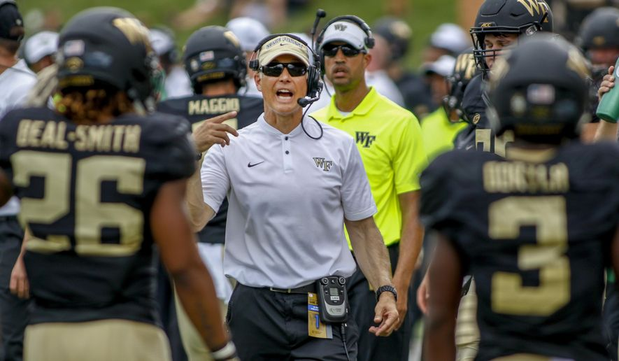 Wake Forest coach Dave Clawson talks to his players in the first half of an NCAA college football game against Towson in Winston-Salem, N.C., Saturday, Sept. 8, 2018. (AP Photo/Nell Redmond)