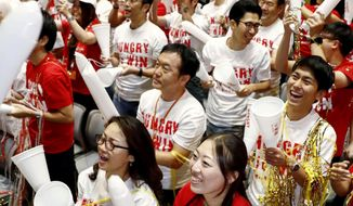 Employees of Nissin Food Products Co., celebrate after the victory of Japan's Naomi Osaka, as they watch the live broadcast of the U.S. Open tennis women's final between Serena Williams of the U.S. and Osaka, at the headquarters of the food company, a sponsor of Osaka, Sunday, Sept. 9, 2018. Japanese tennis and non-tennis fans alike are celebrating one of their own winning a Grand Slam tournament for the first time. (Yuki Sato/Kyodo News via AP)
