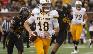 Wyoming quarterback Tyler Vander Waal, center, runs away from Missouri's Adam Sparks, left, and Walter Palmore, right, during the first half of an NCAA college football game Saturday, Sept. 8, 2018, in Columbia, Mo. (AP Photo/L.G. Patterson)