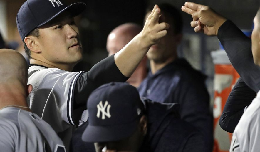 New York Yankees starting pitcher Masahiro Tanaka, left, greets teammates in the dugout after pitching the eighth inning of a baseball game against the Seattle Mariners, Friday, Sept. 7, 2018, in Seattle. The Yankees won 4-0. (AP Photo/Ted S. Warren)
