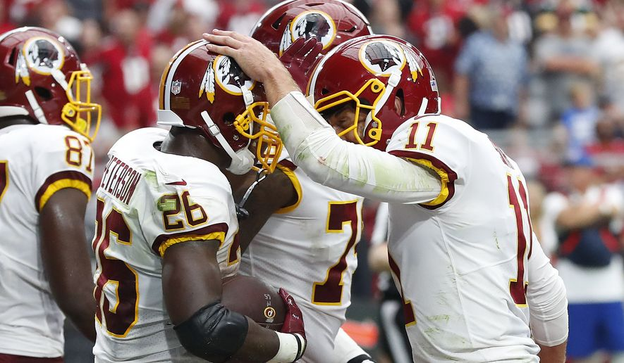 Washington Redskins running back Adrian Peterson (26) celebrates his touchdown run with quarterback Alex Smith (11) during the first half of an NFL football game against the Arizona Cardinals, Sunday, Sept. 9, 2018, in Glendale, Ariz. (AP Photo/Rick Scuteri)