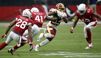 Washington Redskins running back Chris Thompson (25) tries to elude Arizona Cardinals defensive back Antoine Bethea (41),defensive back Jamar Taylor (28) and linebacker Haason Reddick (43) during the first half of an NFL football game, Sunday, Sept. 9, 2018, in Glendale, Ariz. (AP Photo/Ross D. Franklin)