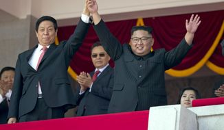 North Korean leader Kim Jong Un, right,  raises hands with China's third highest ranking official, Li Zhanshu, during a parade for the 70th anniversary of North Korea's founding day in Pyongyang, North Korea, Sunday, Sept. 9, 2018. North Korea staged a major military parade, huge rallies and will revive its iconic mass games on Sunday to mark its 70th anniversary as a nation. (AP Photo/Ng Han Guan)