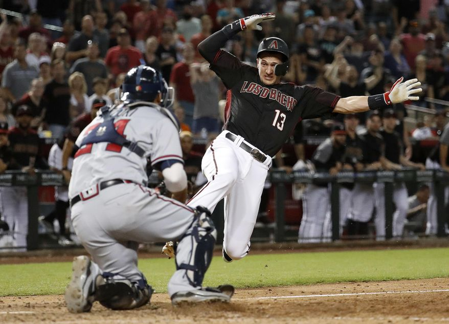 Arizona Diamondbacks Nick Ahmed (13) is tagged out at the plate by Atlanta Braves catcher Kurt Suzuki to end the baseball game Saturday, Sept. 8, 2018, in Phoenix. The Braves won 5-4 in 10 innings. (AP Photo/Matt York)