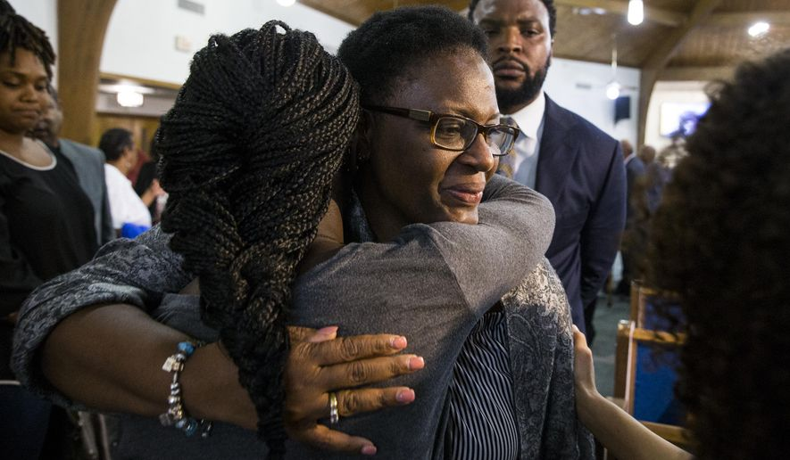 Allison Jean embraces hers son's friends following a prayer vigil for Botham Shem Jean at the Dallas West Church of Christ on Saturday, Sept. 8, 2018 in Dallas. He was shot by a Dallas police officer in his apartment on Thursday night. (Shaban Athuman/The Dallas Morning News via AP)