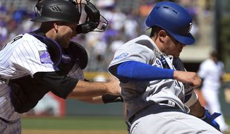 Los Angeles Dodgers' Manny Machado, right, slides into home plate, knocking the ball out of Colorado Rockies catcher Chris Iannetta's glove, to score in the first inning of a baseball game Sunday, Sept. 9, 2018, in Denver. (AP Photo/John Leyba)