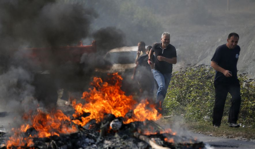 Kosovo Albanians run past a fire burning at a roadblock in Vojtesh, Kosovo, Sunday, Sept. 9, 2018. Kosovo Albanians burned tires and blocked roads with wooden logs, trucks and heavy machinery on a planned route by Serbia's President Aleksandar Vucic who was trying to reach the village of Banje while visiting Serbs in the former Serbian province. (AP Photo/Visar Kryeziu)