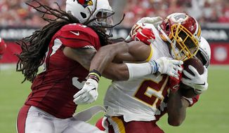 Washington Redskins running back Chris Thompson, center, is hit by Arizona Cardinals defensive back Tre Boston, left, during the first half of an NFL football game, Sunday, Sept. 9, 2018, in Glendale, Ariz. (AP Photo/Rick Scuteri)